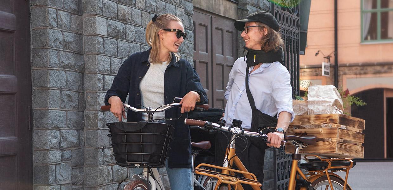 Bild på en tjej och en kille som står tillsammans med cyklar