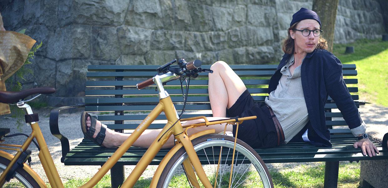 Bild på en kille som sitter på en bänk med sin elcykel.