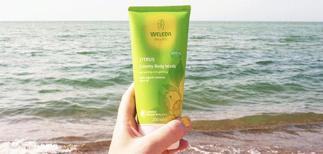 Bild på en hand som håller weleda shower gel mot havet som bakgrund.