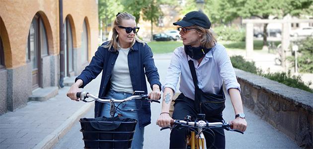 Bild på två personer som sitter på vars en elcykel.