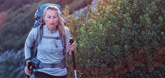 Bild på en kvinna som vandrar med gångstavar