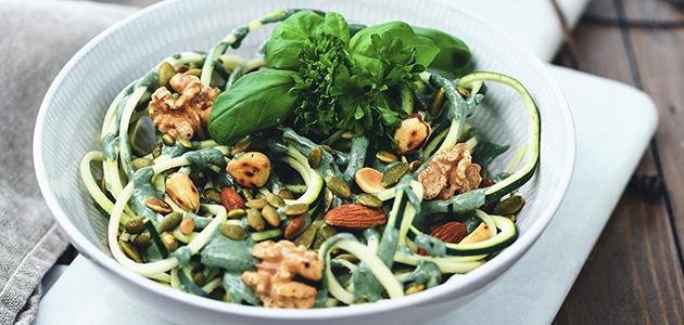 Bild på en skål med en sallad gjord på zuccini, gröna blad och nötter.