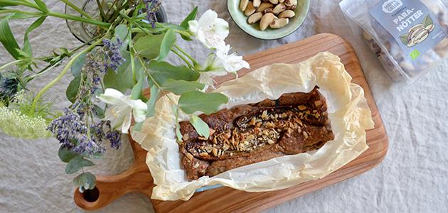 Bild på Happy Greens ekologiska paranötter tillsammans med ett bananbröd på ett bord.