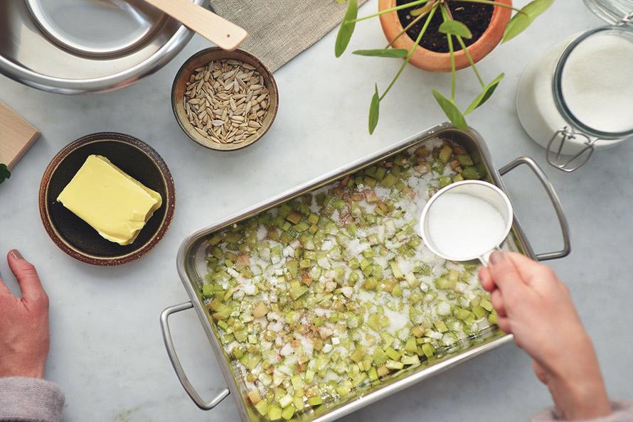 Bild på rabarberpaj och hand som strör socker över pajen.