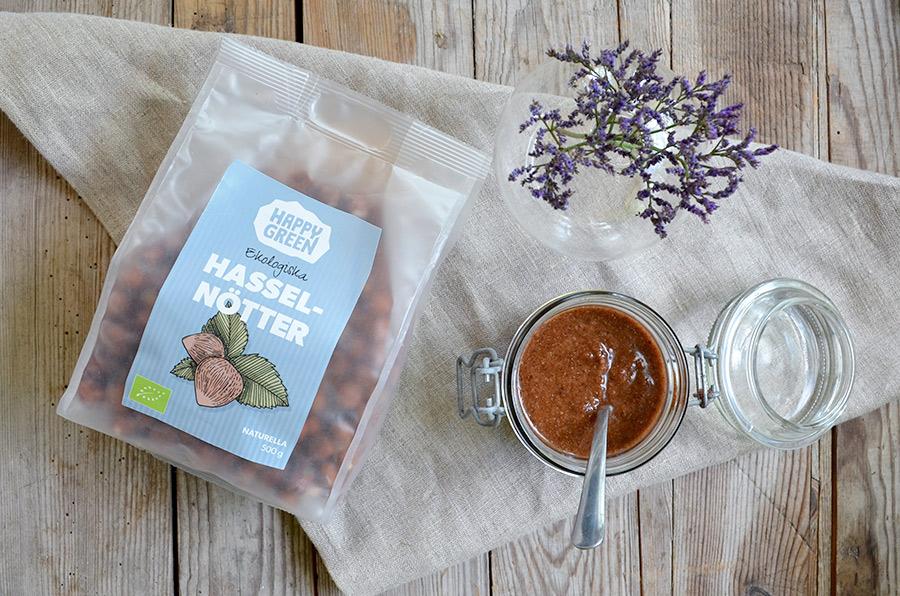 Bild på Happy Greens ekologiska hasselnötter tillsammans med en burk med choklad- och hasselnötssmör.