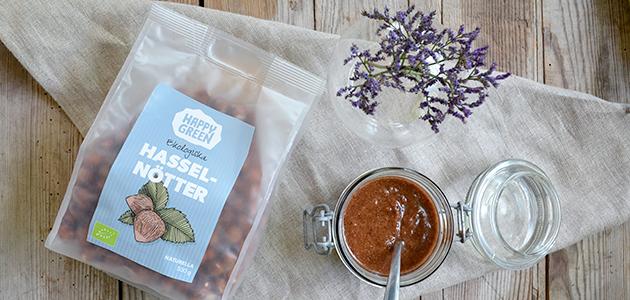 Bild på Happy Greens ekologiska hasselnötter tillsammans med en burk choklad- och hasselnötssmör