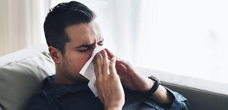 Man med förkylning som snyter sig i engångsnäsduk