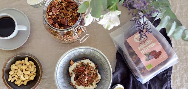 Bild på Happy Greens ekologiska pekannötter tillsammans med en burk granola