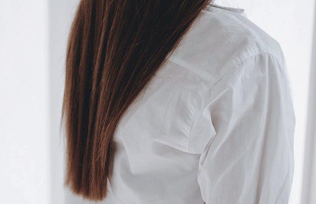 kvinna med långt brunt hår mot en vit vägg