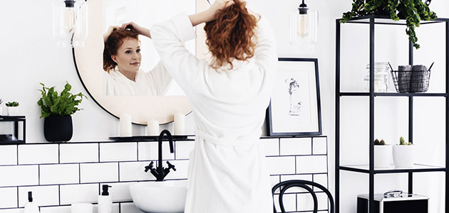 Bild på en kvinna som står och kollar sig i spegeln.