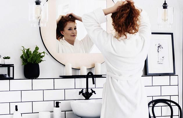 kvinna som står i ett badrum med en vit badrock