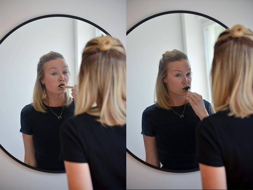 Bild på tjej som borstar tänderna i en spegel.