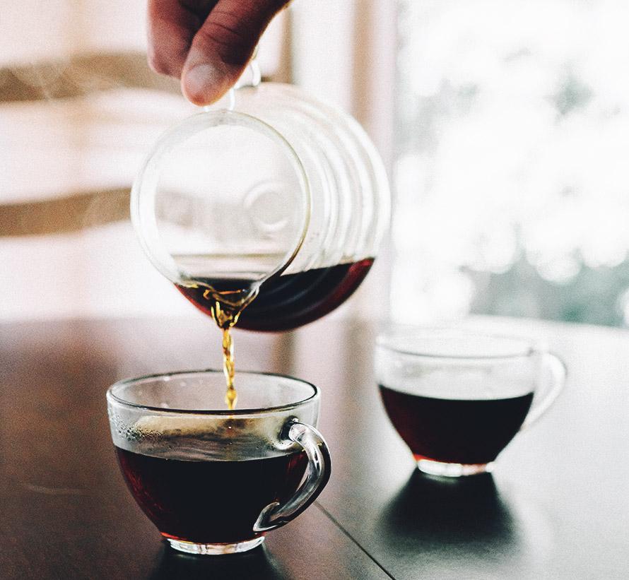 Bild på två koppar med kaffe och en Hario V60 kanna.
