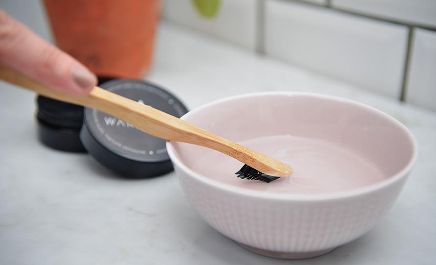 Bild på tandborste som doppas i en skål med vatten.