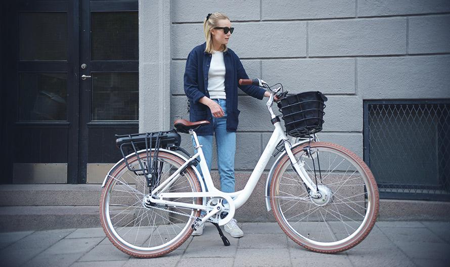 Tjej som står lutad mot en vägg tillsammans med en elcykel från Lifebike, modell Classic G7