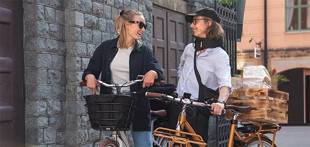 Bild på en tjej och en kille som står tillsammans med vars en elcykel.