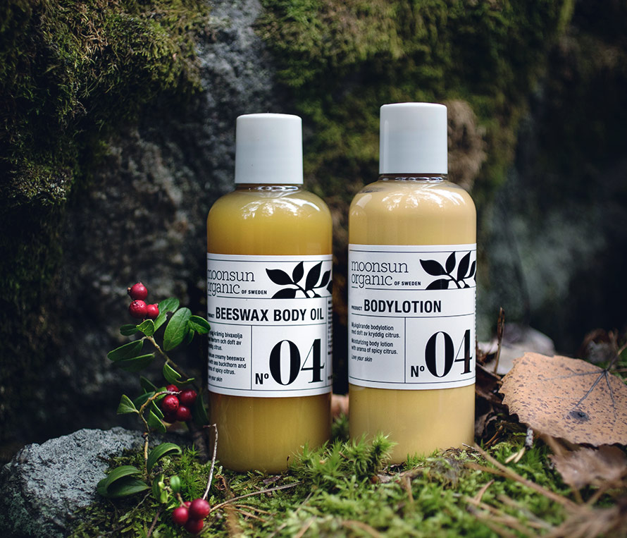Bild på Moonsun Body Beewax Body Oil och Moonsun Body Lotion i skogsmiljö.