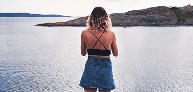Bild på en tjej som står på en klippa och tittar ut över havet.