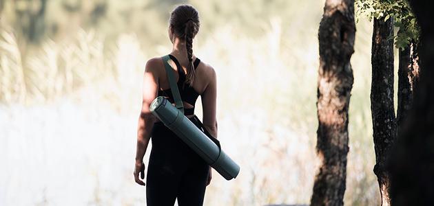 Bild på en tjej som står med en yogamatta på ryggen och kollar ut över en äng.