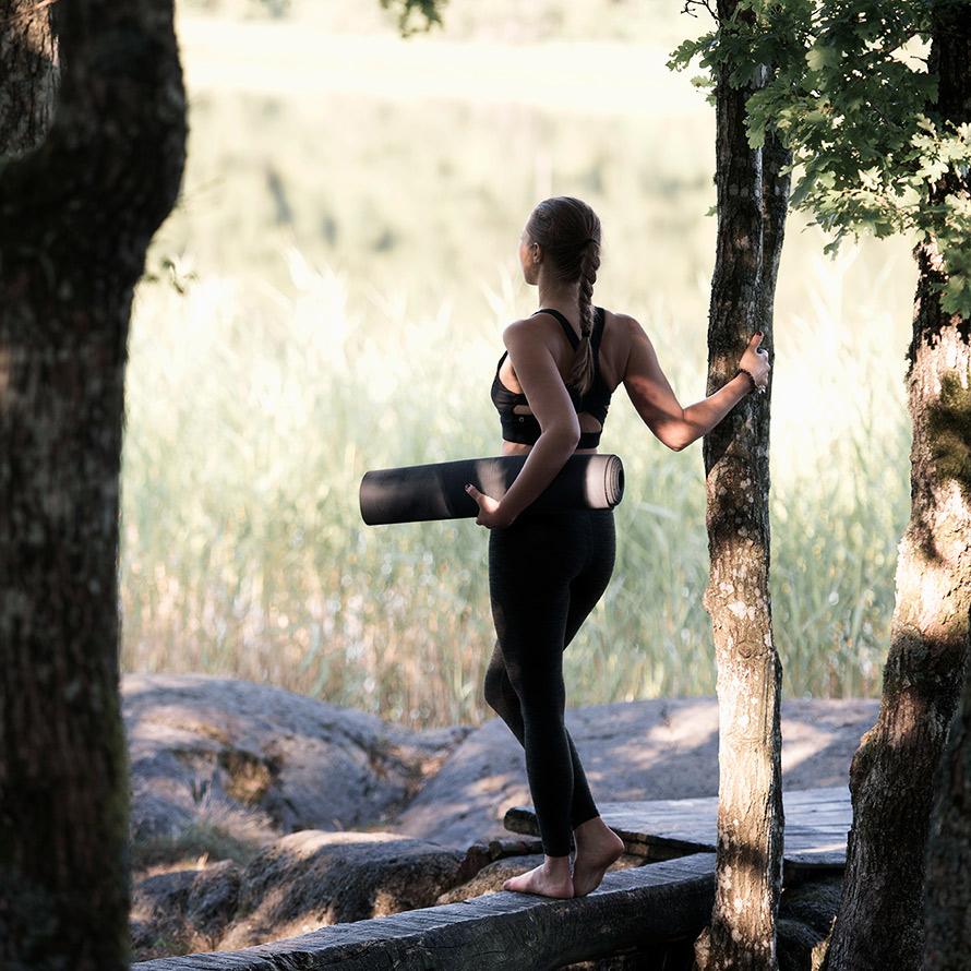 Tjej i yogakläder som bär på en yogamatta och tittar ut mot ett fält.