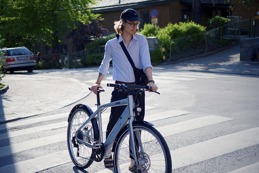 Man som går över gatan med en elcykel från Lifebike, modell C-mute G7