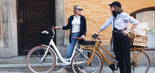 Bild på en tjej och en kille med vars en elcykel.
