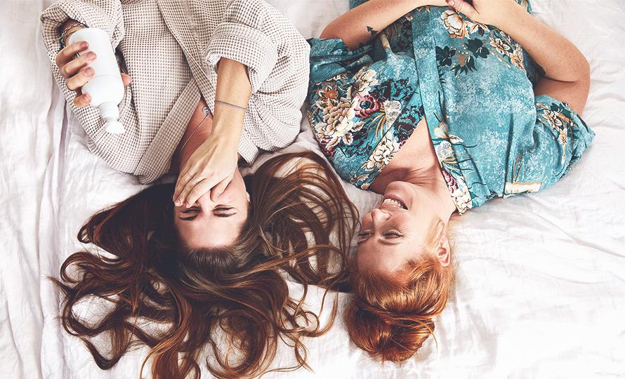 Bild på två glada tjejer som ligger i en säng